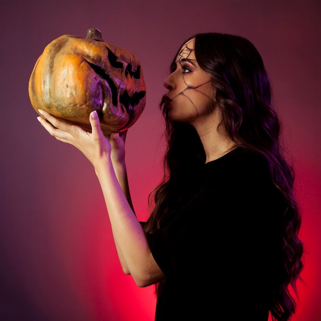 Girl dressed as witch looking at pumpkin Free Photo
