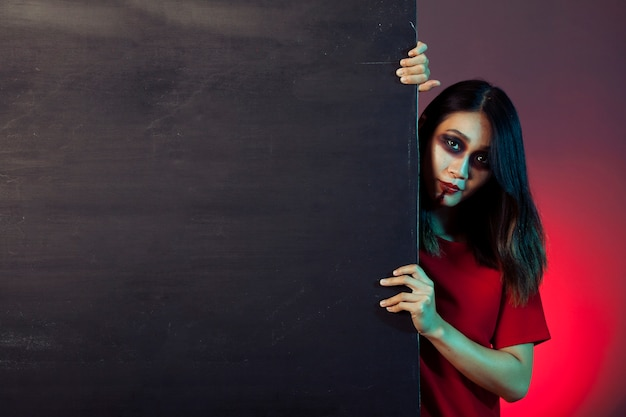 Girl dressed as zombie behind wall Free Photo