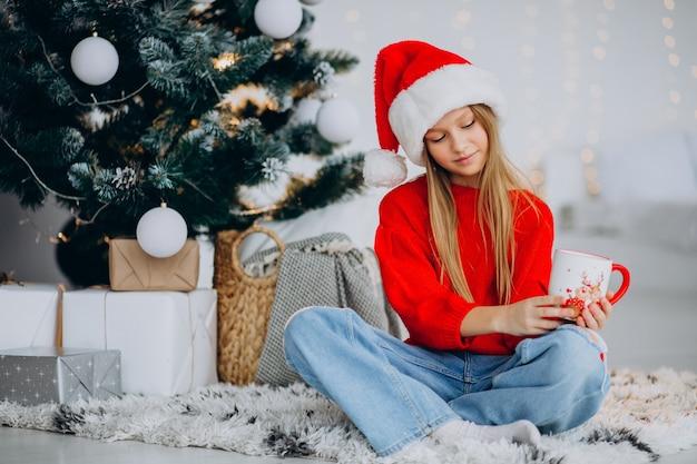 クリスマスツリーでココアを飲む女の子 無料写真