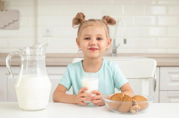 クッキーと牛乳を飲む女の子 Premium写真