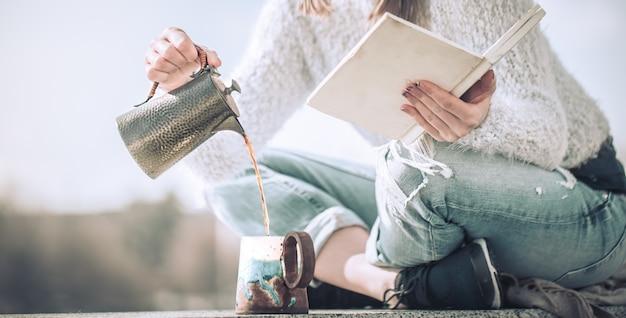 女の子はコーヒーを飲むし、屋外で本を読みます 無料写真