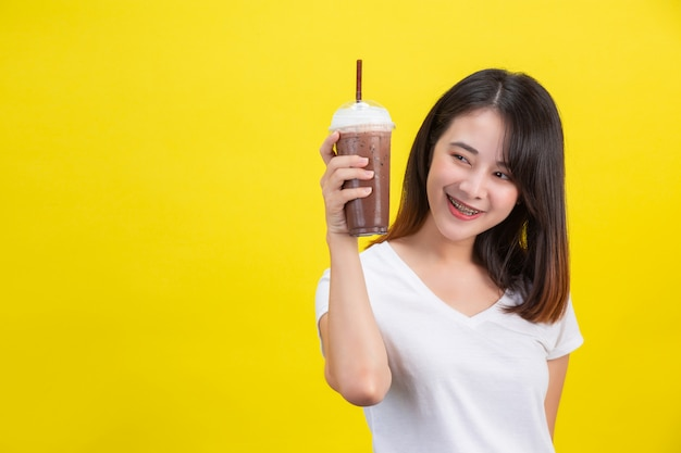 The girl drinks cold water from cocoa from a clear plastic glass on a yellow . Free Photo