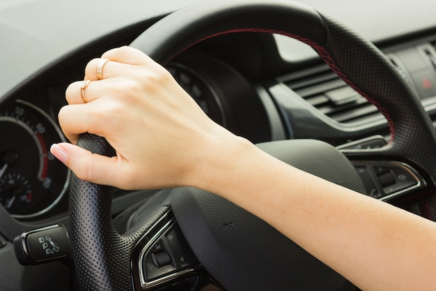 Girl drives a car, holds the steering wheel with one hand Premium Photo