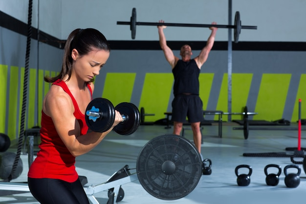 Girl dumbbell and man weight lifting bar workout Premium Photo