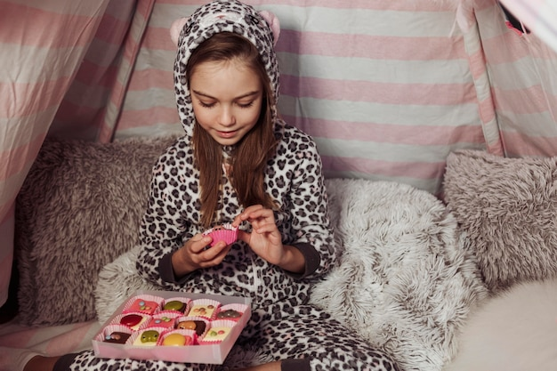 Ragazza che mangia caramelle in una tenda al chiuso Foto Gratuite