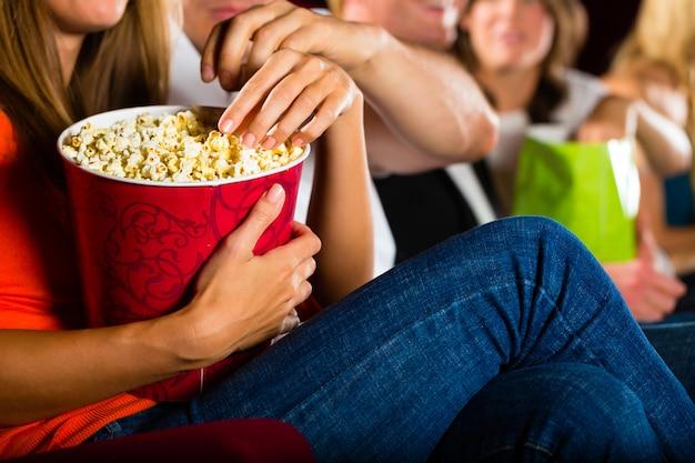 Girl eating popcorn in cinema or movie theater Premium Photo