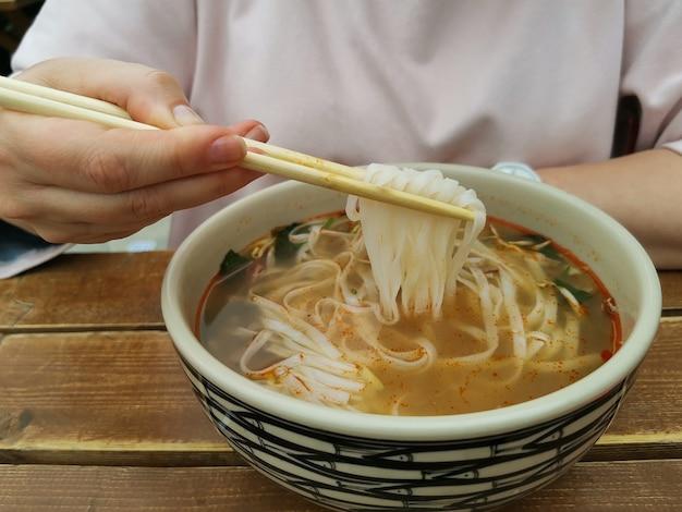 거리 카페에서 젓가락으로 쌀 국수를 먹는 소녀. 프리미엄 사진