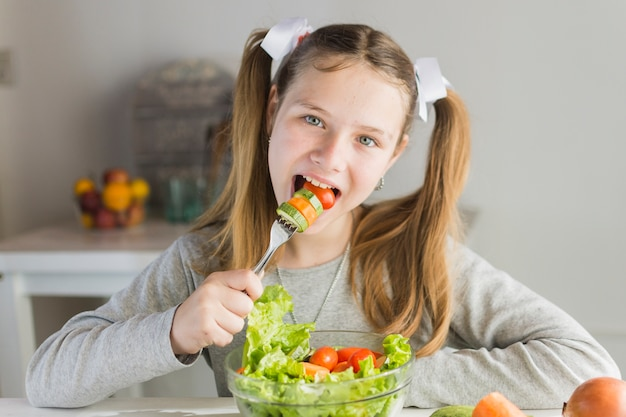 girl eating vegetable salad with fork photo free download
