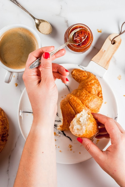 Girl eats homemade continental breakfast, croissants, coffee. jam on white marble table, copyspace top view, hands in picture Premium Photo