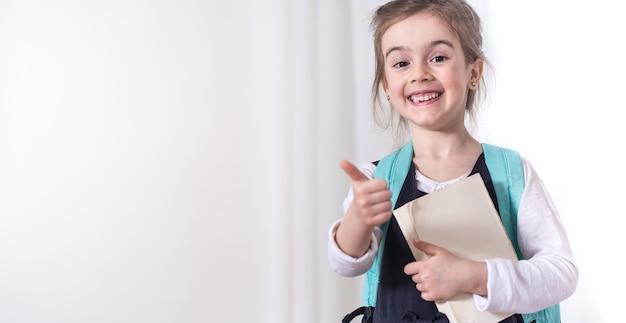 バックパックと明るい背景に本を持つ女子小学生。教育と小学校のコンセプトです。テキストのための場所。 無料写真