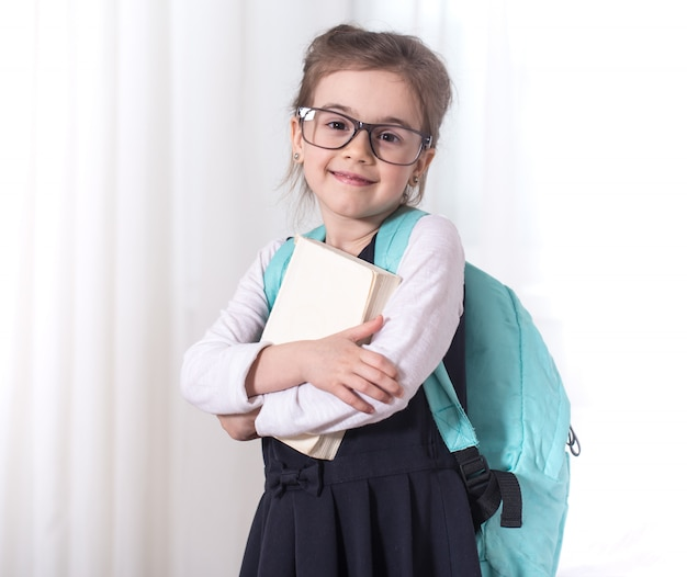 Studente della scuola elementare con uno zaino e un libro Foto Gratuite