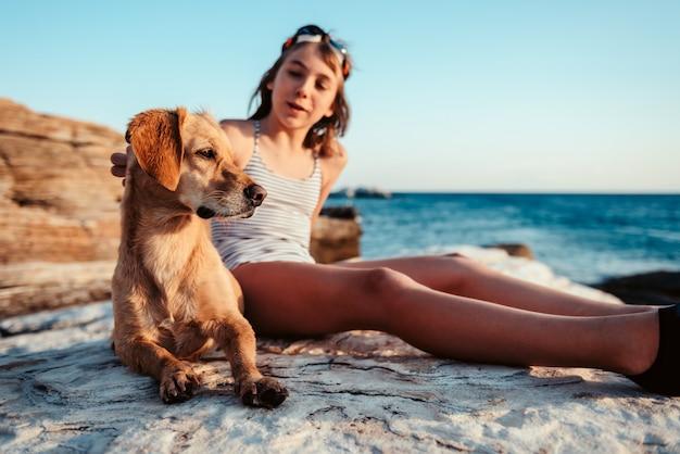 Girl embracing her dog on the beach Premium Photo
