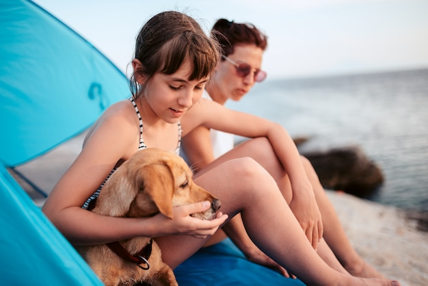 Girl embracing her dog while sitting inside beach tent with mother Premium Photo