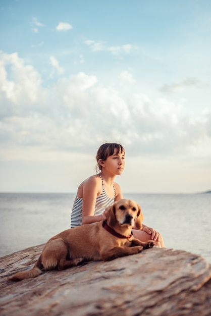 Girl embracing her dog while sitting on the rock by the sea Premium Photo