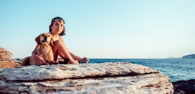 Girl embracing her dog while sitting on the rocky beach Premium Photo