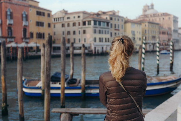 Girl enjoying canal view with boat passing by in venice, italy. Premium Photo