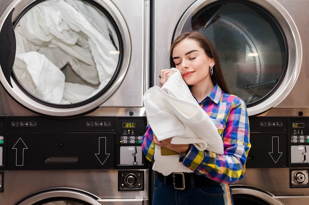 Girl enjoys clean and smelling towels after washing in launderette Premium Photo