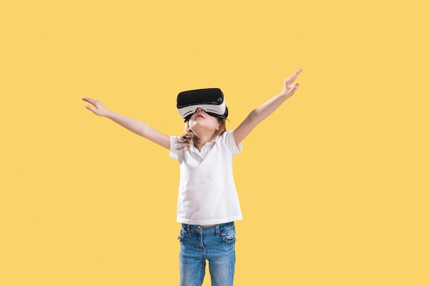 Girl   experiencing vr headset game on colorful . surprised emotions on her face.child using a gaming gadget for virtual reality. Premium Photo