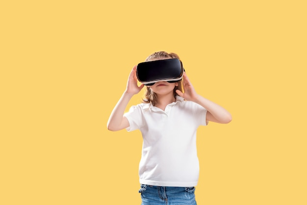 Girl experiencing vr headset game. surprised emotions on her face.child using a gaming gadget for virtual reality. Premium Photo
