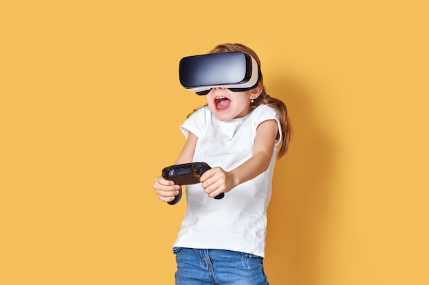 Girl experiencing vr headset vs joystick game. surprised emotions on her face. child using a gaming gadget for virtual reality. Premium Photo
