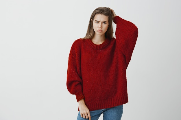 Girl feeling bothered not knowing answer to question. portrait of displeased gloomy european woman in trendy loose sweater, scratching back of head and frowning, confused and troubled over gray wall Free Photo