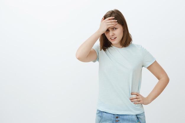 大学の近くでママを見て屈辱を感じている女の子。不快な額の下から見ている額に手のひらで顔を覆っているtシャツで不快で恥ずかしいかわいい若い女性 無料写真