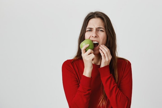 Girl feeling toothache and grimacing from pain as biting green apple Free Photo