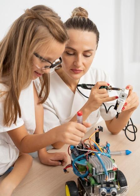 Ragazza e insegnante femminile che fanno esperimenti scientifici con auto robotica Foto Gratuite