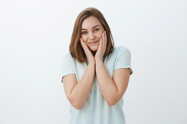 La ragazza finalmente si sbarazza dell'acne con la nuova maschera facciale. affascinante donna lieta e brillante che tocca le guance e sorride con gioia sentendosi bella e fresca per risolvere i problemi della pelle in posa contro il muro grigio Foto Gratuite