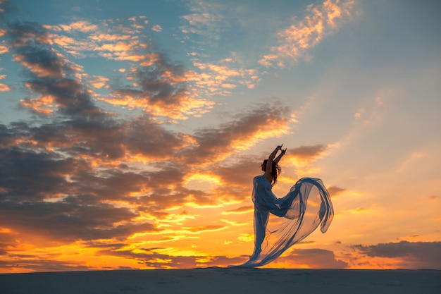 A girl in a fly white dress dances and poses in the sand desert at sunset Premium Photo