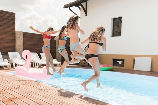 Girl friends jumping in swimming pool Free Photo