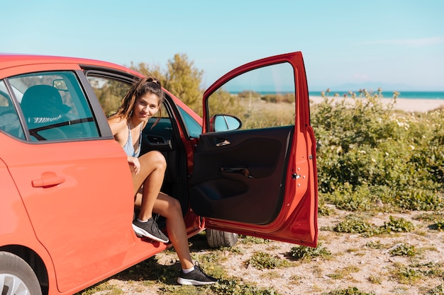 Girl getting out of car and looking at camera Free Photo