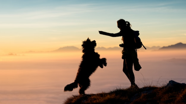 Girl gives food to his dog in the mountains Premium Photo