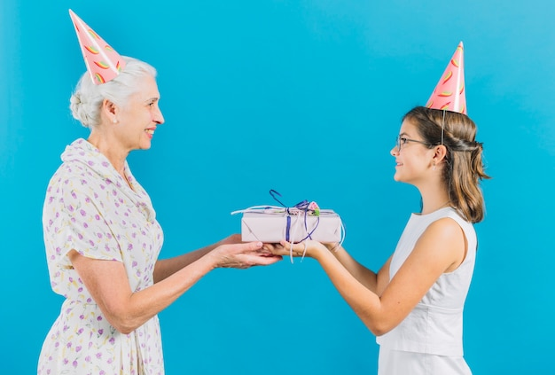 Girl Giving Birthday Gift To Her Grandmother On Blue Background Free Photo