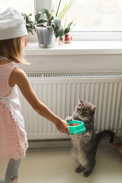 Girl giving food to her cat Free Photo