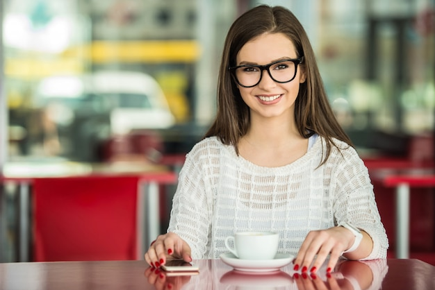 Girl in glasses and white pullover sitting in urban cafe. Premium Photo