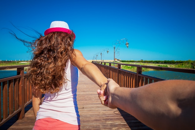 A girl goes on a post holding a fellow on a hand Premium Photo