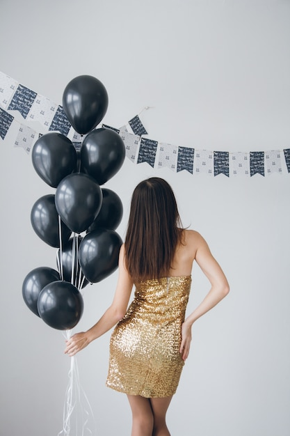 Girl in a gold dress with black balloons Premium Photo