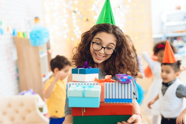 Girl in green festive hat rejoices at huge number of gifts. Premium Photo