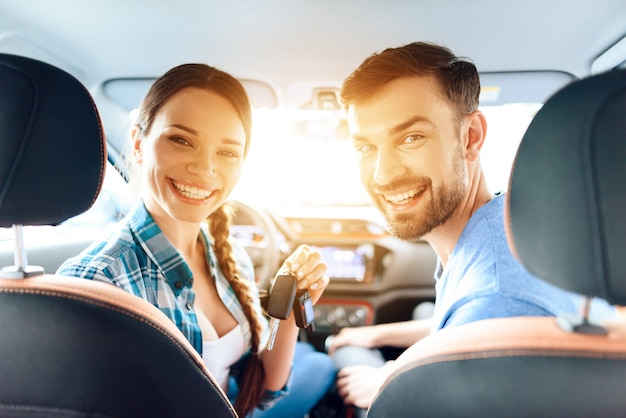 Girl and the guy are sitting in a new car and smiling. Premium Photo