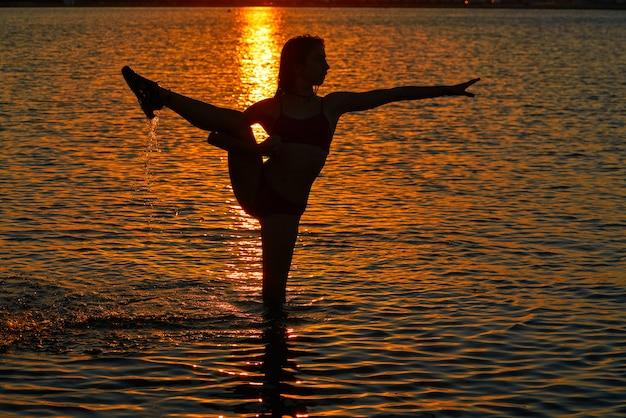 Girl gymnastics pose at sunset beach Premium Photo