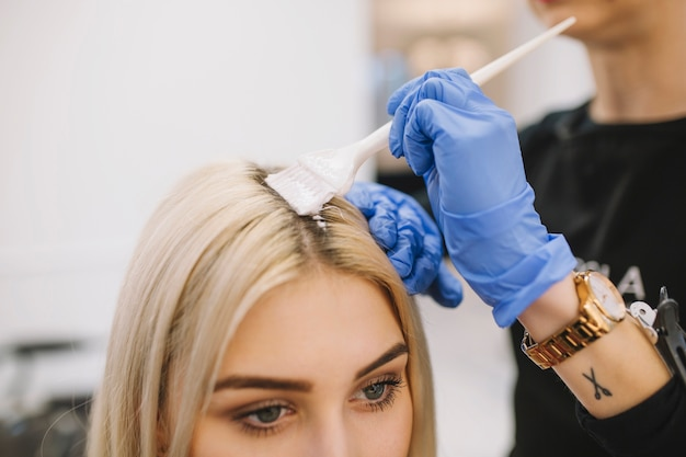 Girl in hairdresser parlor having coloring procedure Free Photo