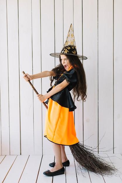 Girl in halloween costume imitating broom flight in studio Free Photo
