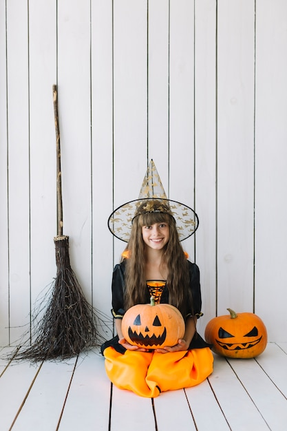 Girl in halloween costume sitting in studio with pumpkins and broom Free Photo