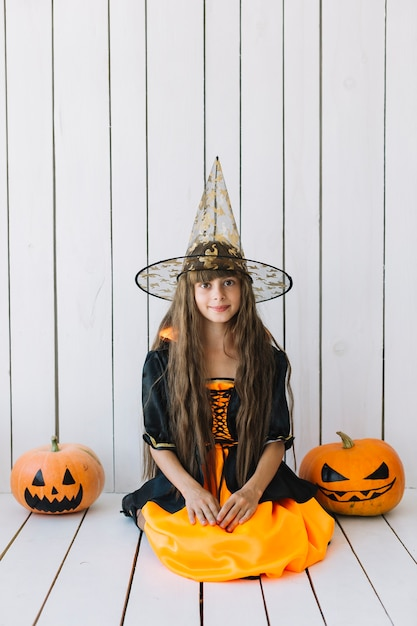Girl in halloween costume with pumpkins on sides sitting in studio Free Photo