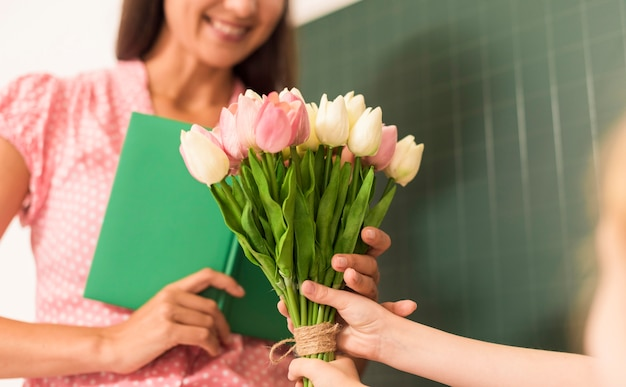 Girl handing a bouquet of flowers to her teacher Free Photo