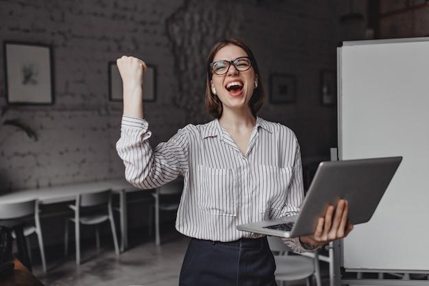 女の子は喜んで悲鳴を上げ、ボードの背景に対してオフィスでラップトップを持ってポーズをとって、勝利の手のジェスチャーをします。 無料写真