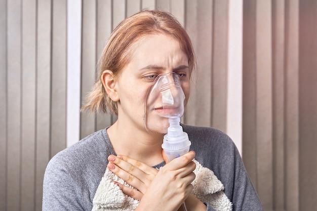 У девочки приступ астмы, и она использует маску небулайзера, которую используют при лечении респираторных заболеваний, чтобы остановить приступ. Premium Фотографии
