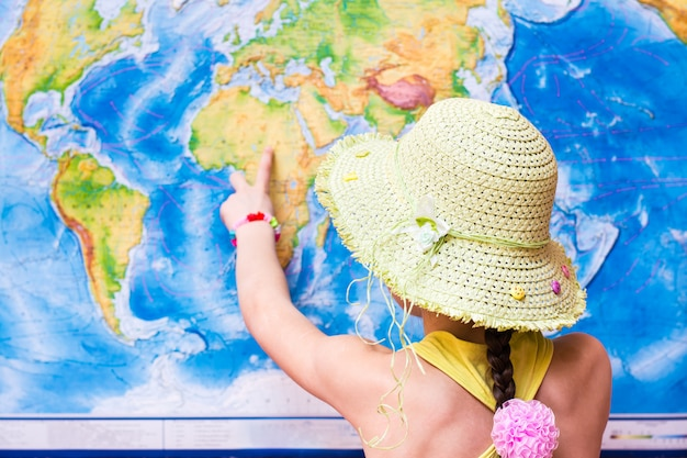 Girl in a hat points to a world map with a finger Premium Photo