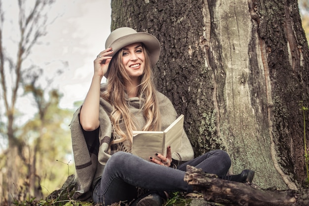 Girl in a hat reading a book in autumn forest Free Photo
